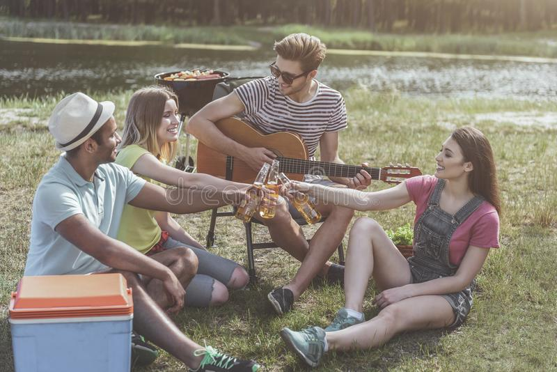 Tevreden vrienden het feesten gebeurtenis door de rivier royalty-vrije stock afbeelding