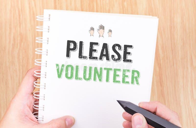 Tevreden vrijwilligerswoord op het witte notitieboekje van het ringsbindmiddel met hand ho stock foto