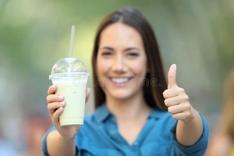 Tevreden vrouw die een smoothie met omhoog duimen houden stock foto