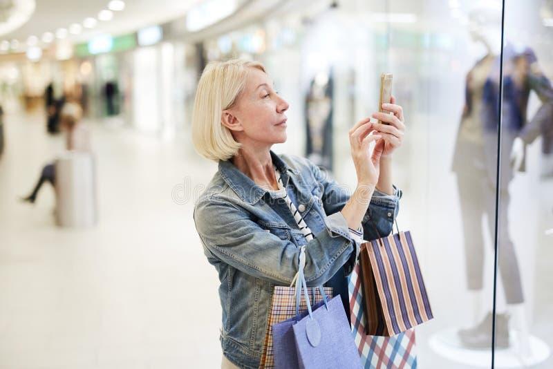 Tevreden vrouw die favoriete uitrusting in wandelgalerij fotograferen stock afbeeldingen