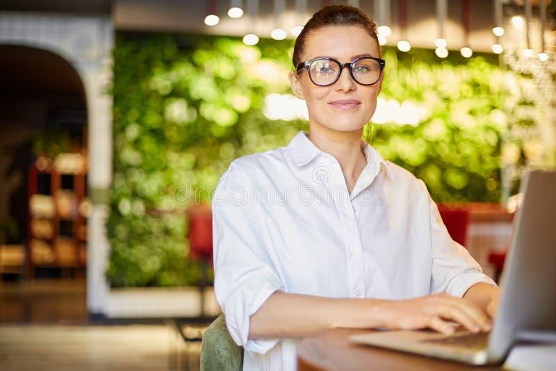 Tevreden vrouw die met laptop bij camera glimlachen royalty-vrije stock afbeeldingen