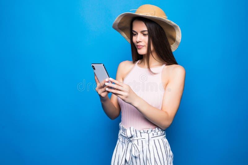 Tevreden vrouw het typen sms-bericht of het scrollen door sociale netwerken die die smartphone gebruiken over blauwe achtergrond  stock afbeeldingen