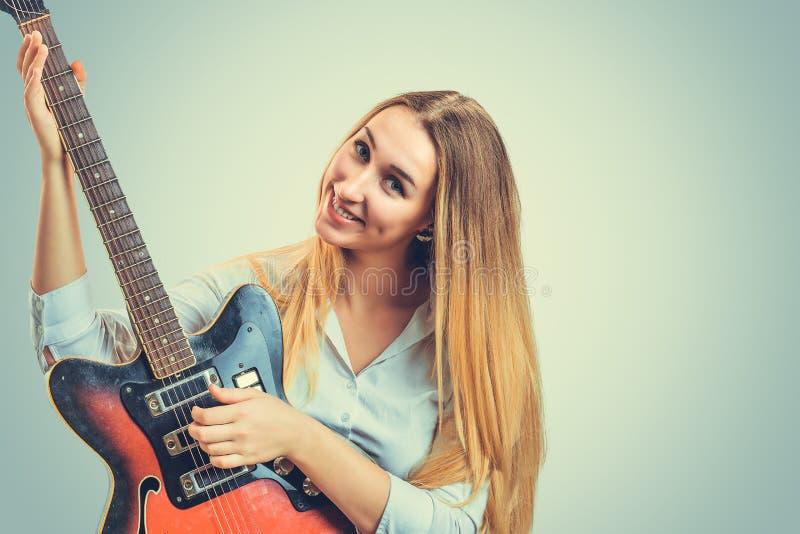 Tevreden vrouw met elektrische gitaar stock afbeeldingen