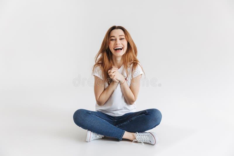 Tevreden vrouw in t-shirtzitting op vloer met wapens samen stock foto