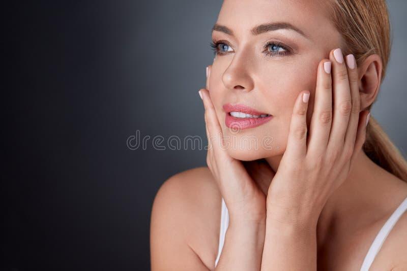 Tevreden vrouw wat betreft gezicht royalty-vrije stock fotografie