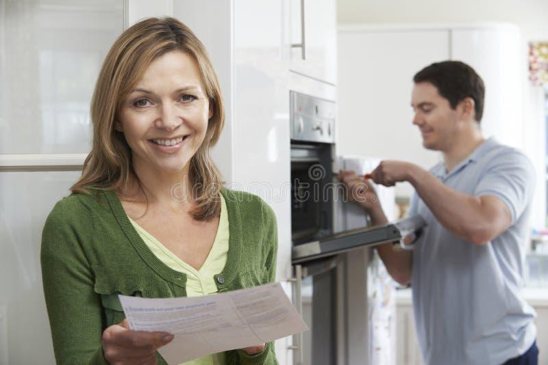 Tevreden Vrouwelijke Klant met Oven Repair Bill stock afbeelding
