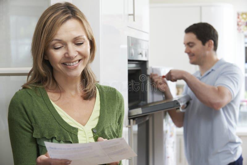 Tevreden Vrouwelijke Klant met Oven Repair Bill stock foto