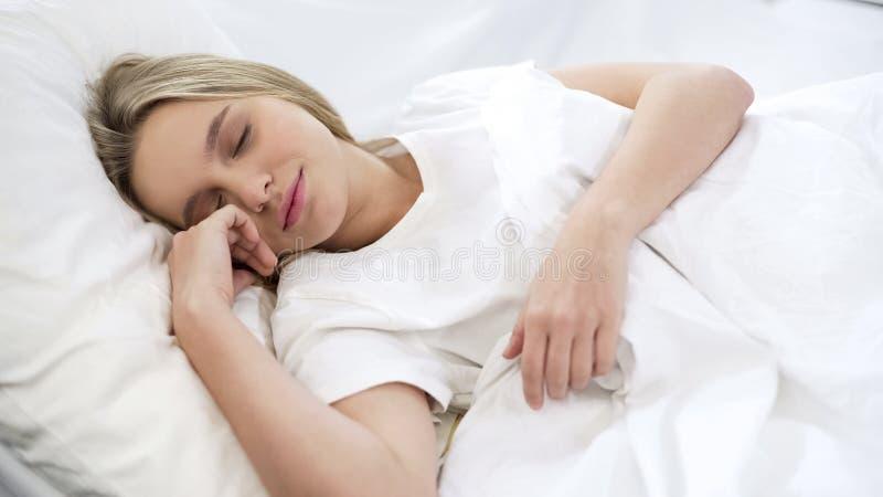 Tevreden vrouwenslaap in bed, ontspanningstijd, die na harde bezige week rusten stock afbeeldingen