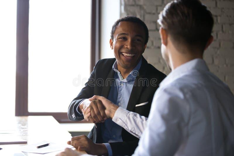 Tevreden zwarte cliënt het schudden handen die manager danken voor goede D stock foto