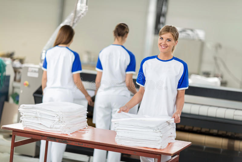 Tewerkgestelde de vrouwen keuren het strijken textiel goed royalty-vrije stock afbeeldingen