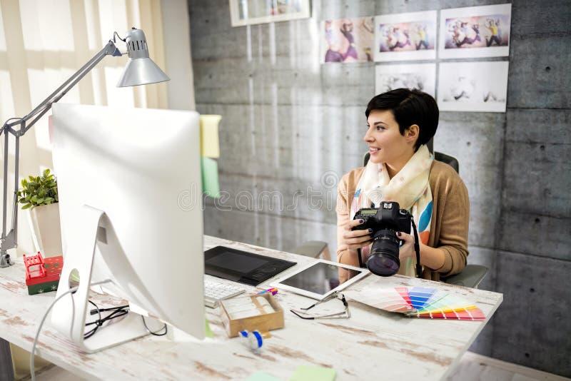 Tewerkgestelde vrouw die in fotostudio werken royalty-vrije stock afbeelding