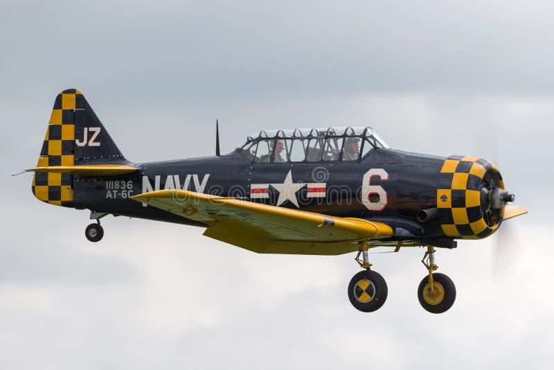 Texan de AT-6C SNJ/Harvard norteamericanos G-TSIX en marcas de la marina de guerra de los E.E.U.U. en acercamiento a la tierra imagenes de archivo