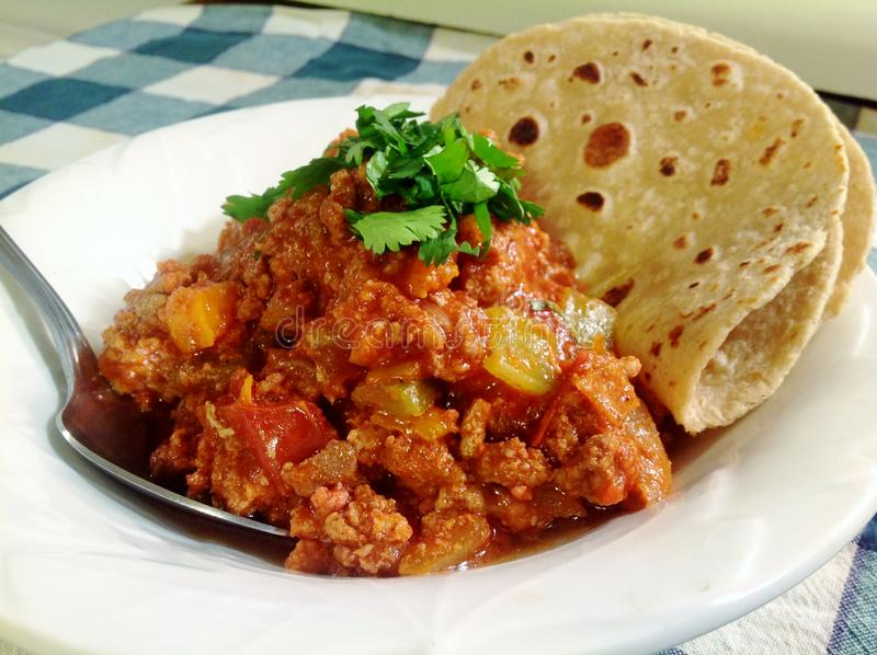 Texas All Meat Chili. Texas all meat beanless chili served in a white bowl with a toasted flour tortilla and garnished with cilantro royalty free stock image
