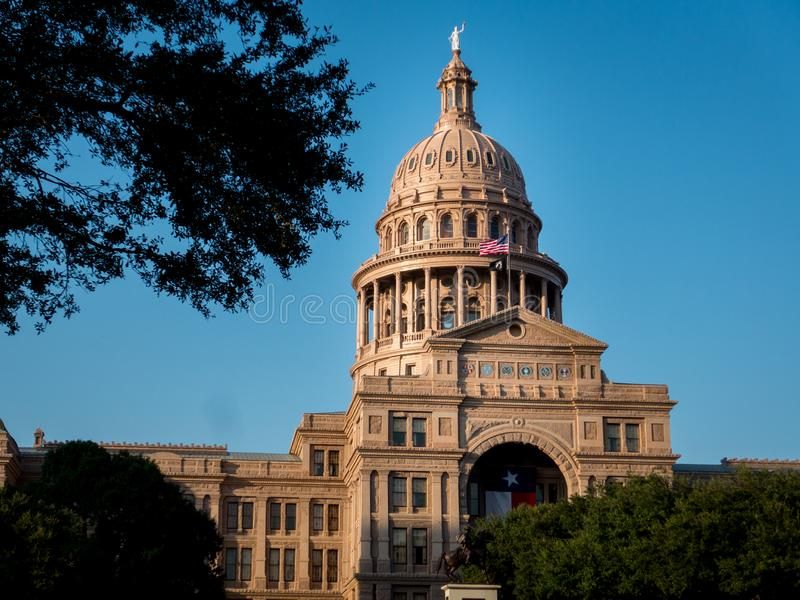 Texas capital in Austin with texas state flag, trees in foreground and clear blue sky royalty free stock images