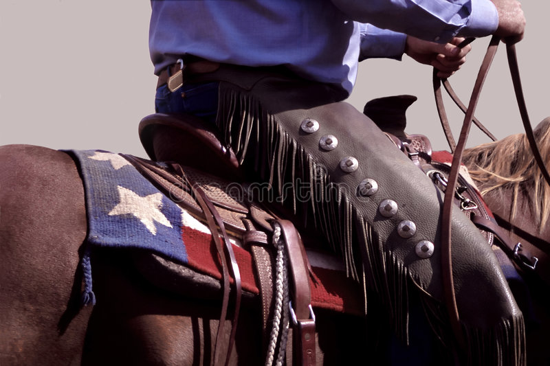 Texas Cowboy. Cowboy wearing chaps on horse with design of Texas flag on saddle blanket