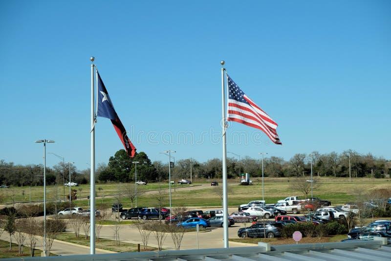 Texas en Amerikaanse vlaggen die in de wind meer dan een parkeerterrein blazen royalty-vrije stock foto
