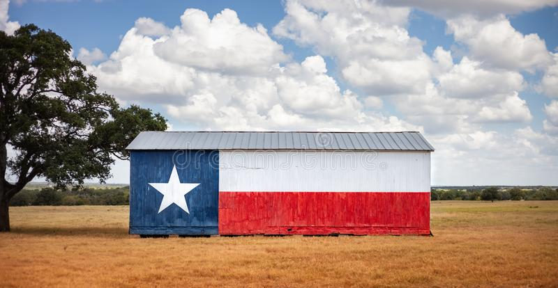 Texas flag painted on old barn. American farmers background, rural scene.  royalty free stock photo