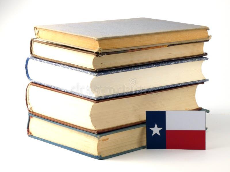 Texas flagga med högen av böcker på vit bakgrund royaltyfri fotografi