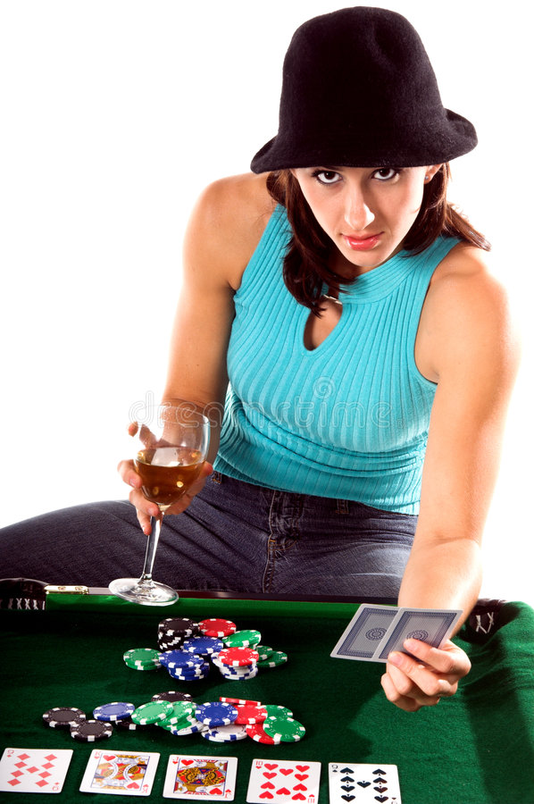 Texas Hold Um. A young brunette playing Texas Holdum Poker and drinking a glass of wine royalty free stock photo