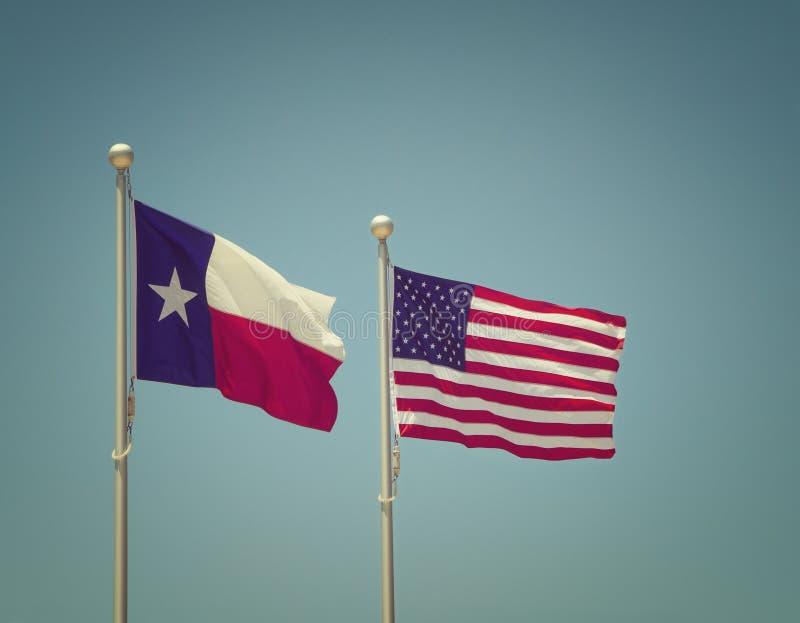 Texas och Förenta staternaflaggorna sid - förbi - sidan royaltyfria foton