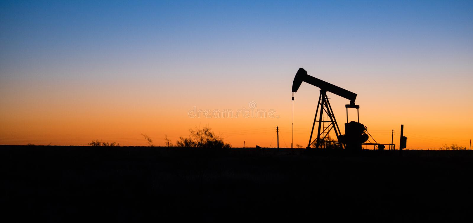 Texas Oil Pump Jack Fracking Crude Extraction Machine Sunset. A device used for oil exploration in Texas stock image
