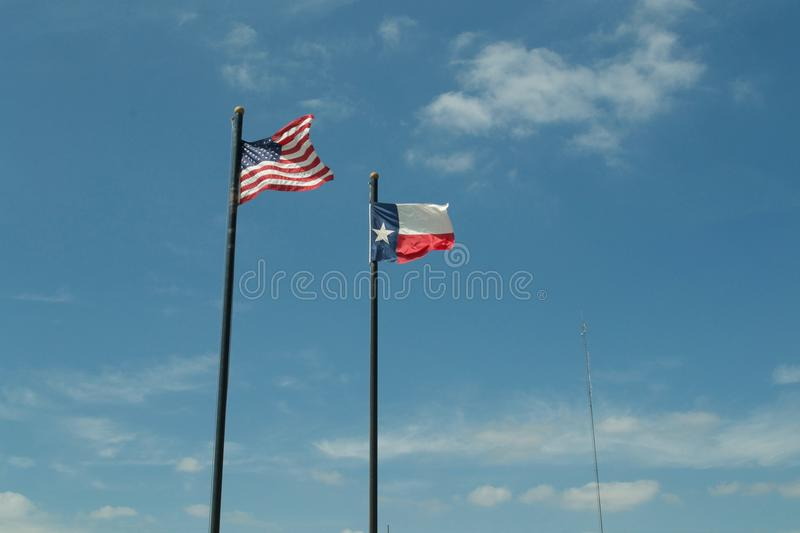 Texas and United States Flags with Blue Sky and Clouds. The Texas state flag and American USA flag with blue sky with a few clouds. Taken in Jasper, Texas royalty free stock image