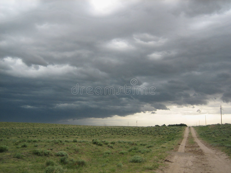 Texas Storm. Heavy dark storm clouds hang over a dirt track road in a flat Texas landscape royalty free stock image