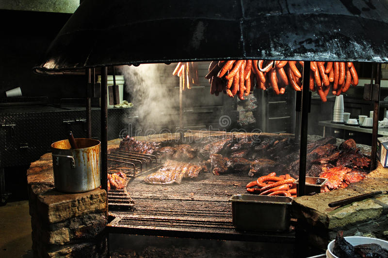 Texas Style Barbecue Pit. Sausages hanging over brisket smoking over a large BBQ pit stock image
