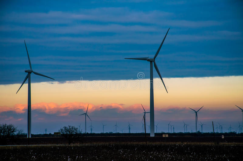 Texas Wind Energy Turbine Farm at Twilight Dusk. Texas Wind Energy Turbines across the Sunrise. As the sun came up the clouds broke and the wind picked up , the stock image