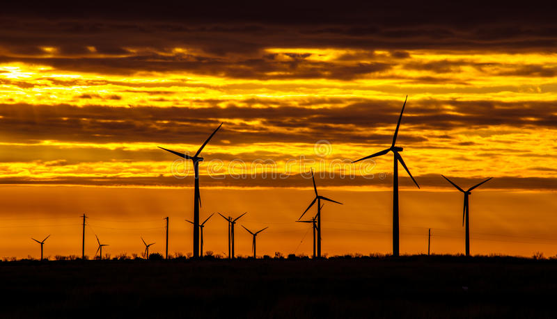Texas Wind Energy Turbines across the Sunrise. As the sun came up the clouds broke and the wind picked up , the energy created by wind turbine farms , like royalty free stock image