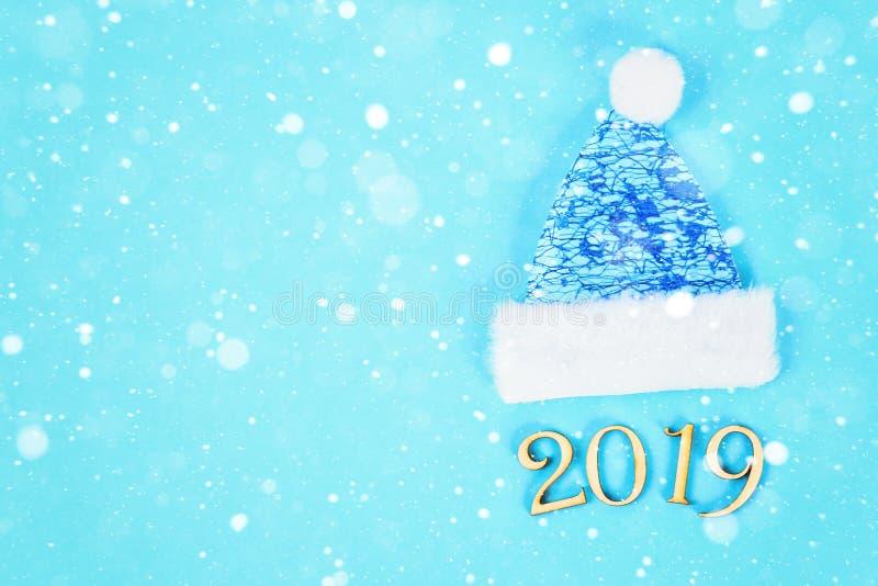 Text 2019 år Övervintra locket och tumvantet på en blå bakgrund Bästa sikt, lekmanna- lägenhet royaltyfri foto