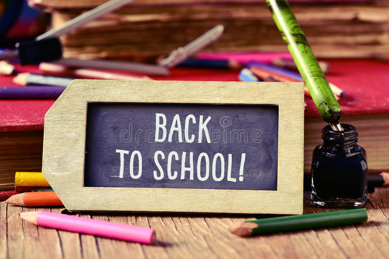 Text back to school in a label-shaped chalkboard. Label-shaped chalkboard with the text back to school, some old books and old stationery such as a pen nib or royalty free stock images