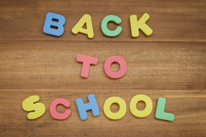 Text back to school made from foam alphabet on wooden background royalty free stock photos