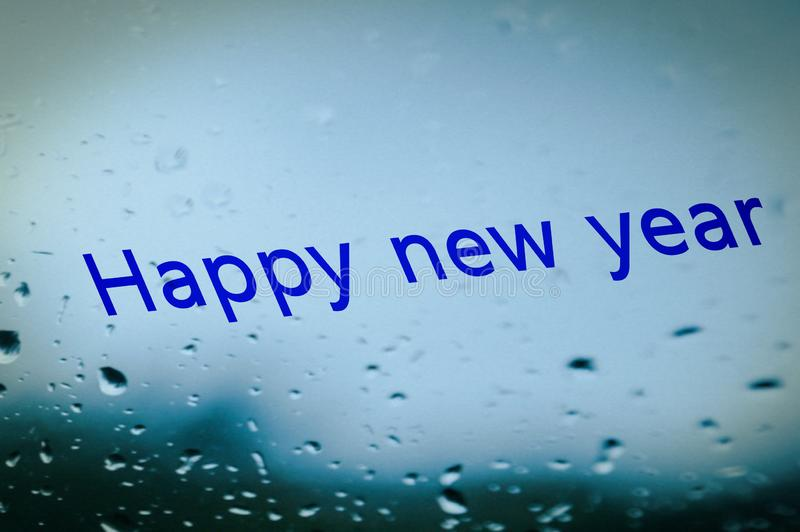 Text background of happy new year in raindrops royalty free stock photography