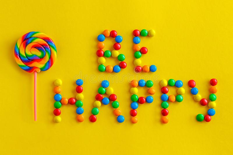 Text be happyand colored lollipop on a yellow background. Text `be happy` from colorful candies and colored lollipop on a yellow background royalty free stock photos