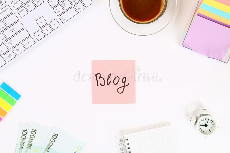 Text blog on a sticker note on a white desktop next to a coffee mug and a keyboard. Top view, flat layout. Text blog on a sticker note on a white desktop next royalty free stock images