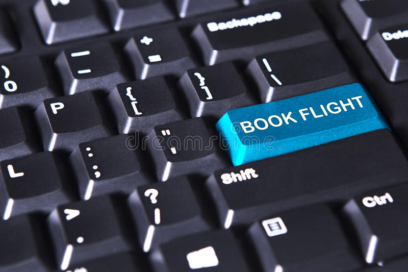 Text of book flight on the blue button. Image of blue button with text of book flight on the modern keyboard stock photography