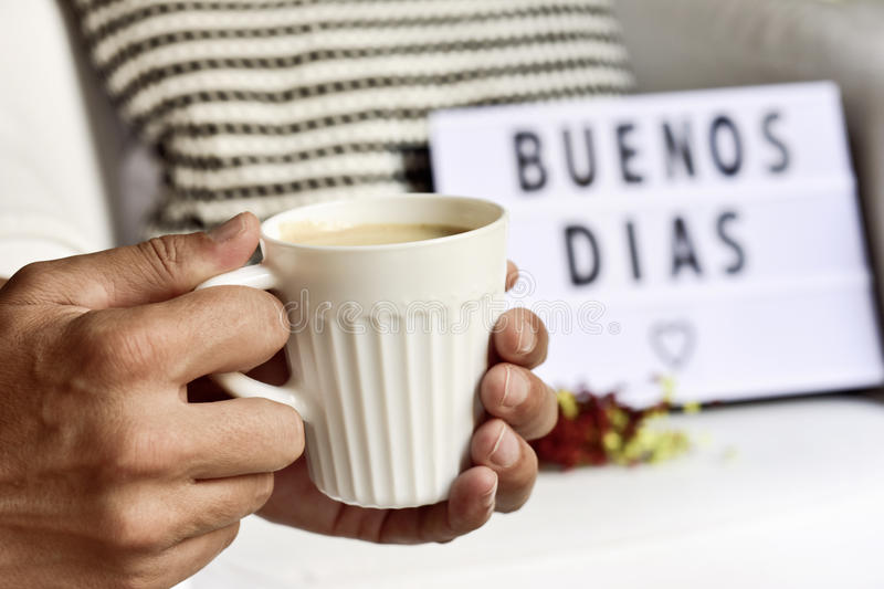 Text buenos dias, good morning in Spanish. Closeup of a young man with a white ceramic cup with coffee in his hand and a lightbox in the background with the text stock images