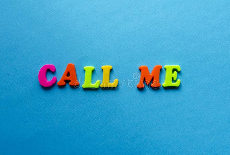 Text call me from plastic colored letters on blue paper background stock photo