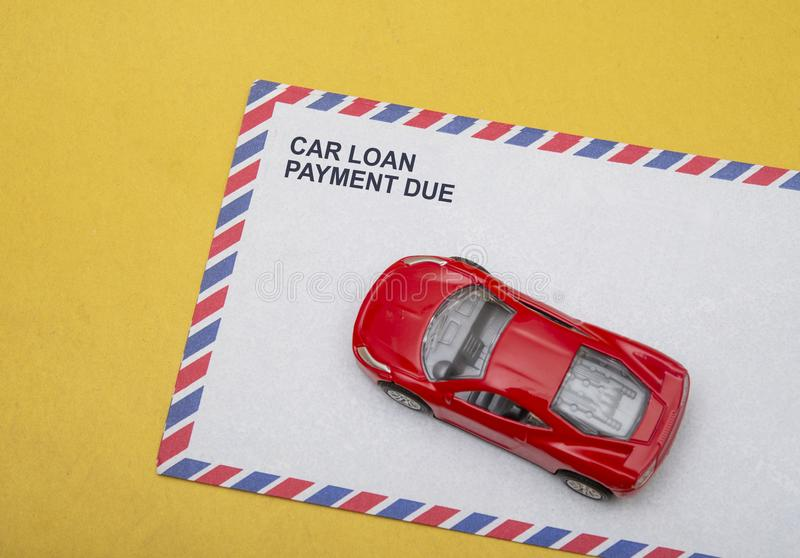 Text of car loan payment due with post card on yellow background.  stock photography