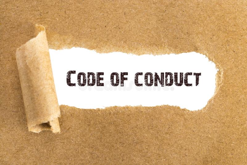 The text Code of conduct appearing behind torn brown paper stock photography