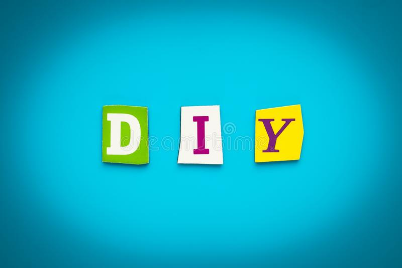 Text - D I Y - from colorful letters on blue background. Single word on banner. Message on poster. Abbreviation - Do It Yourself. stock photos