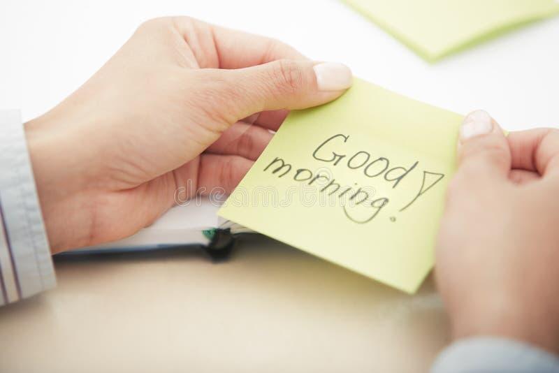 Text des gutenmorgens auf klebendem Papier stockbild