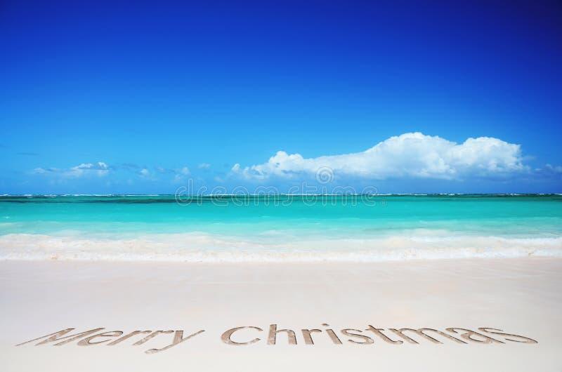 Text des tropischen Strandes und der frohen Weihnachten stockfoto