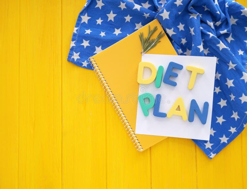 Text DIÄT-PLAN gemacht von den Farbbuchstaben und -notizbuch auf Farbholztisch stockfoto