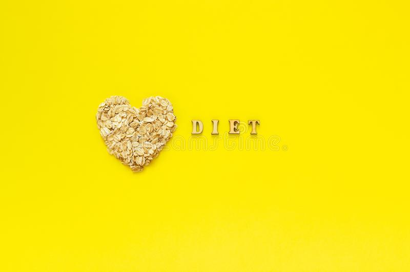 Text Diet and oat flakes in shape heart on yellow background. Text Diet and oatmeal oat flakes in shape heart on yellow background. Helthy organic diet concept stock photography