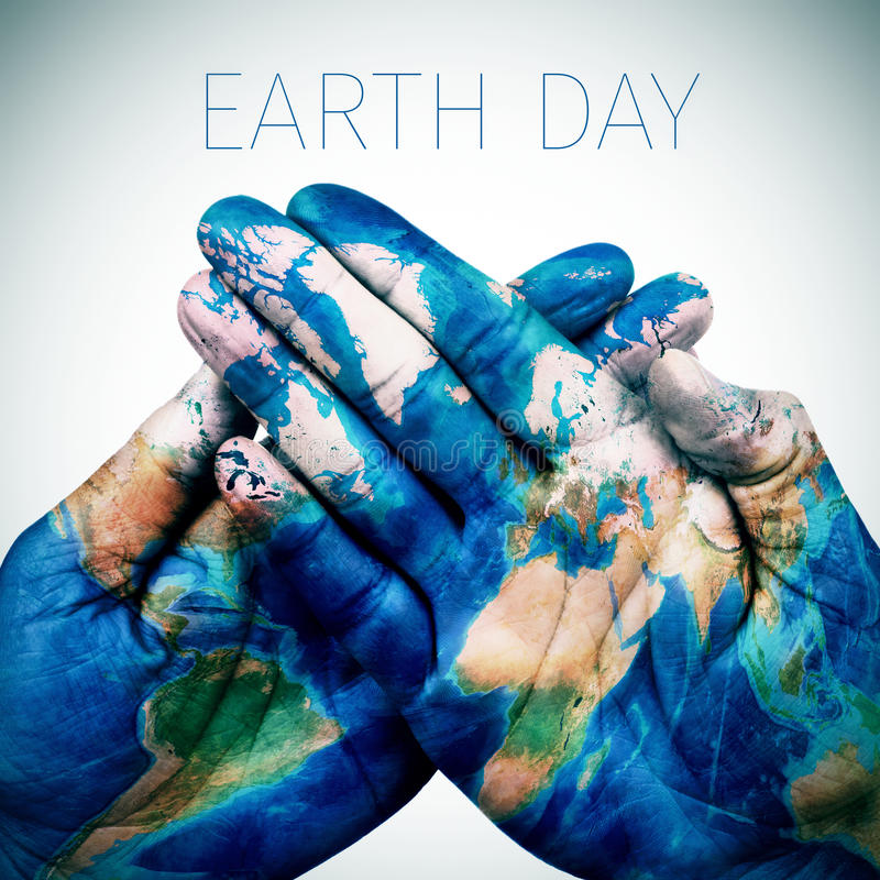 text earth day and man hands patterned with a world map (furnished by NASA) royalty free stock photo