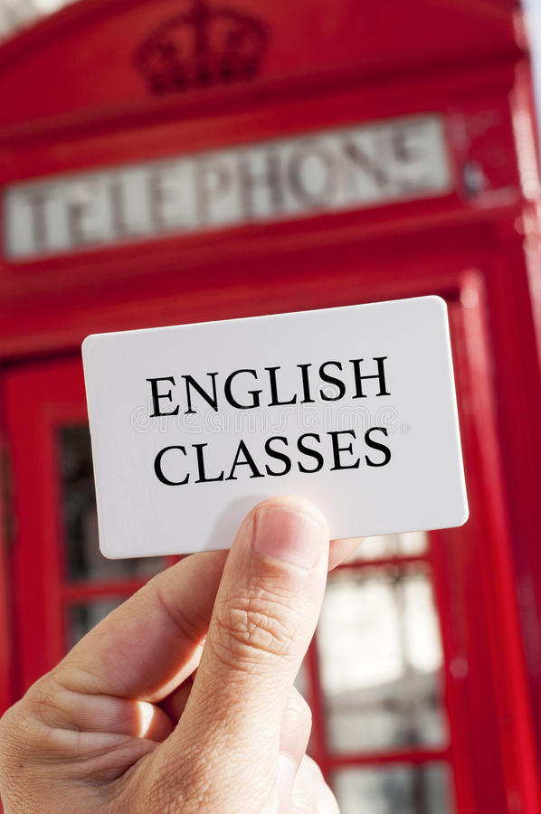 Text english classes in a signboard and a red telephone booth. The hand of a man holding a signboard with the text english classes written in it, with a typical royalty free stock images