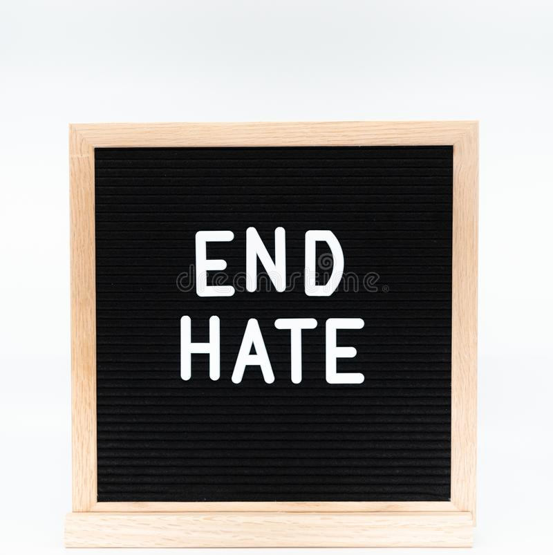 Text in english spelling `End Hate` on black felt board in a wooden frame. Letter Board on white background. A sign with a messa royalty free stock photos