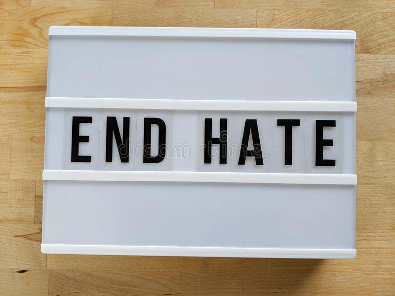 Text in english spelling `End Hate` on a lightbox against wood  background stock images